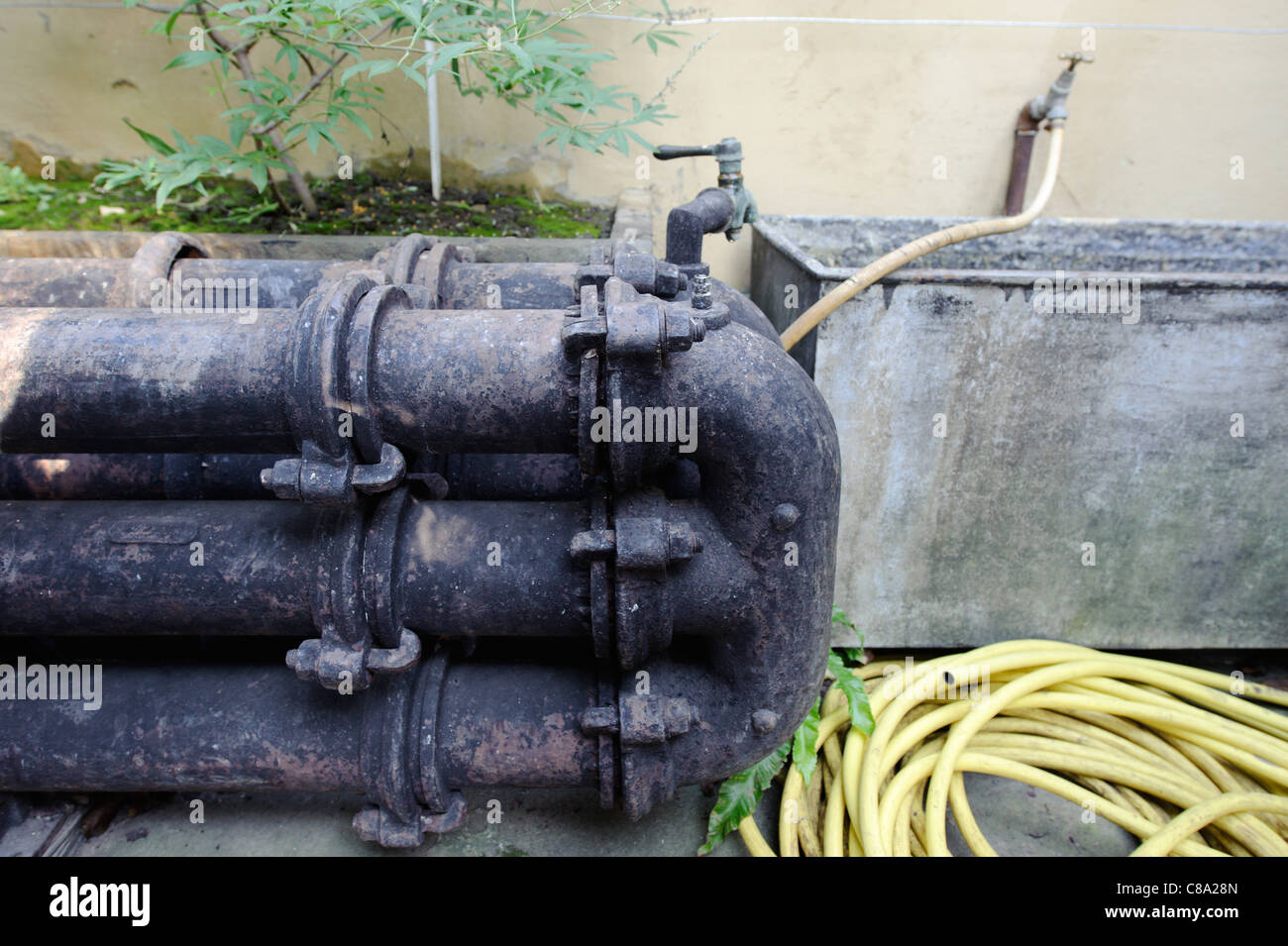 Old cast iron triple greenhouse hot water heating system - Stock Image