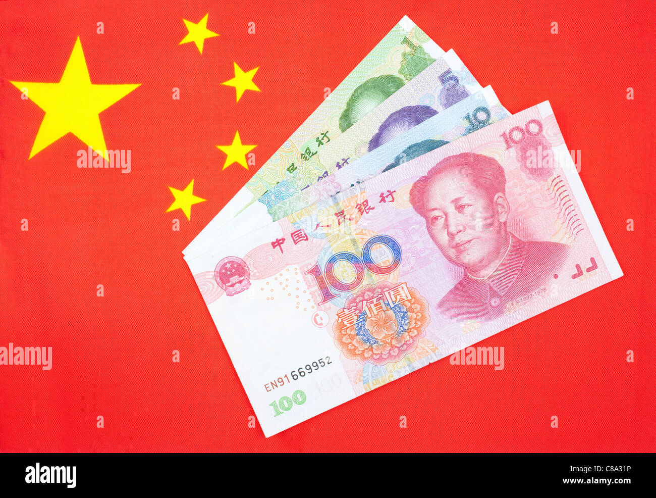 Chinese currency Yuan notes on the chinese flag - Stock Image