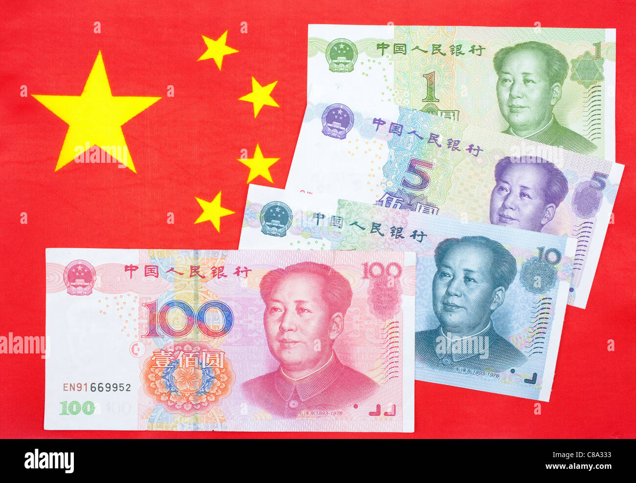 chinese currency yuan notes on the chinese flag stock photo
