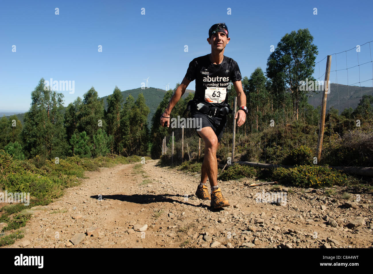 Man walking uphill in cross country trail race - Stock Image