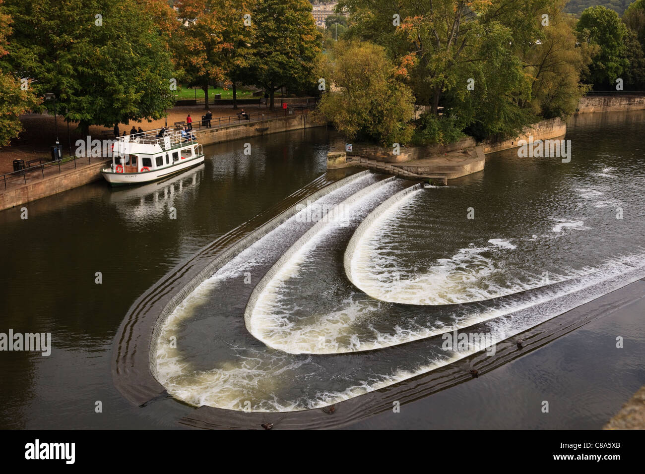 Tourist sightseeing cruise boat moored on the River Avon by Pulteney weir in Bath Somerset England UK Britain - Stock Image