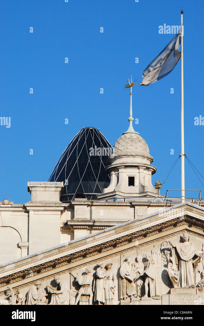Skyline view in the City of London financial center showing the tympanum of the Royal Exchange and the 'Gherkin' - Stock Image