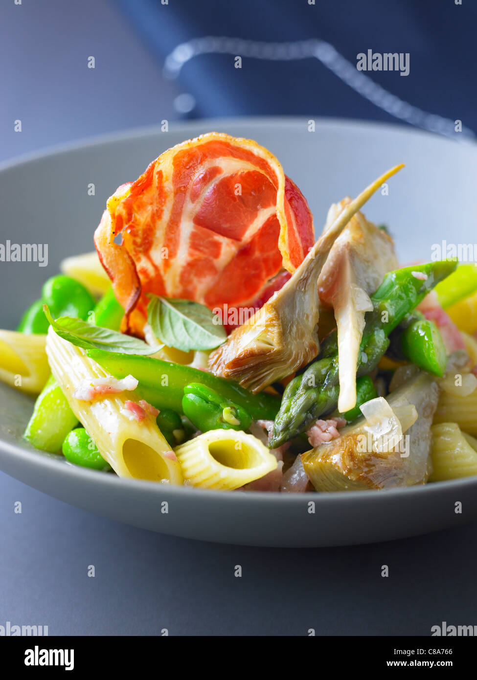Pennes with broad beans,artichokes,asparagus and pancetta Stock Photo