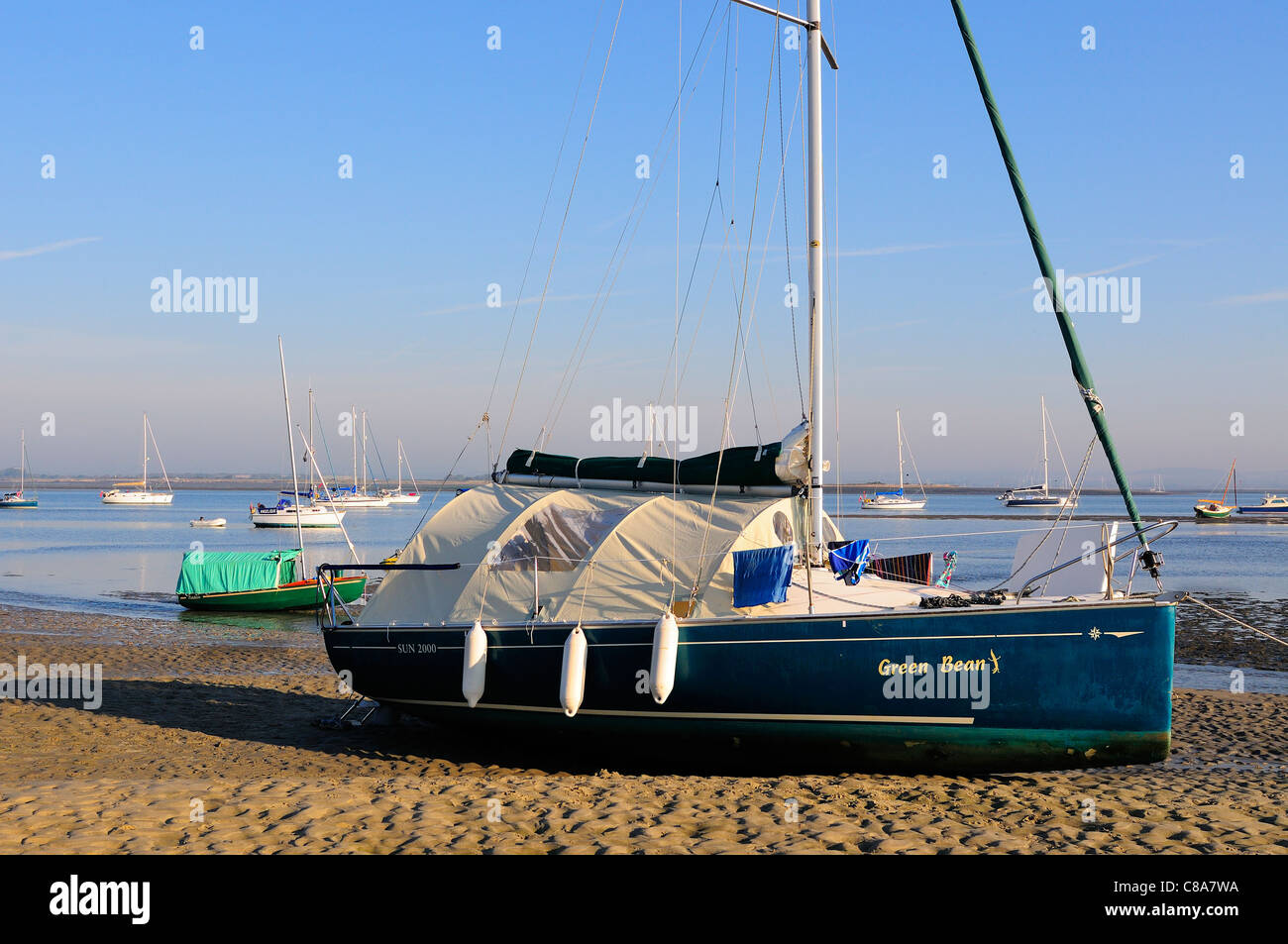 Wayfarer cruising dinghy with awning tent , and small yacht camping  over night at East Head in Chichester Harbour - Stock Image