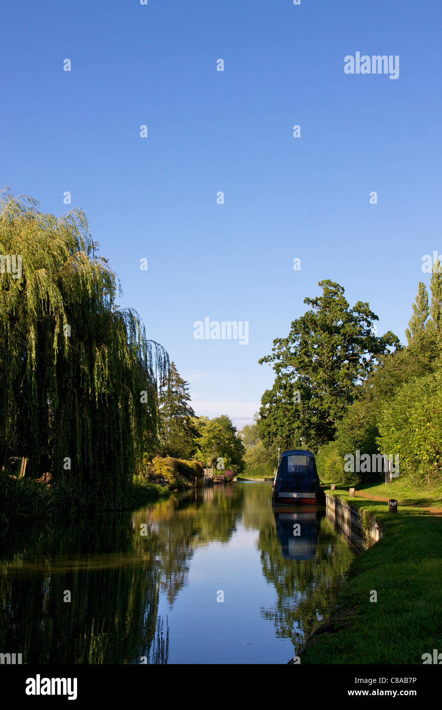Sun setting over moored narrow boats on the Oxford Canal at Cropredy. Deep bluesky, trees and clear reflections - Stock Image