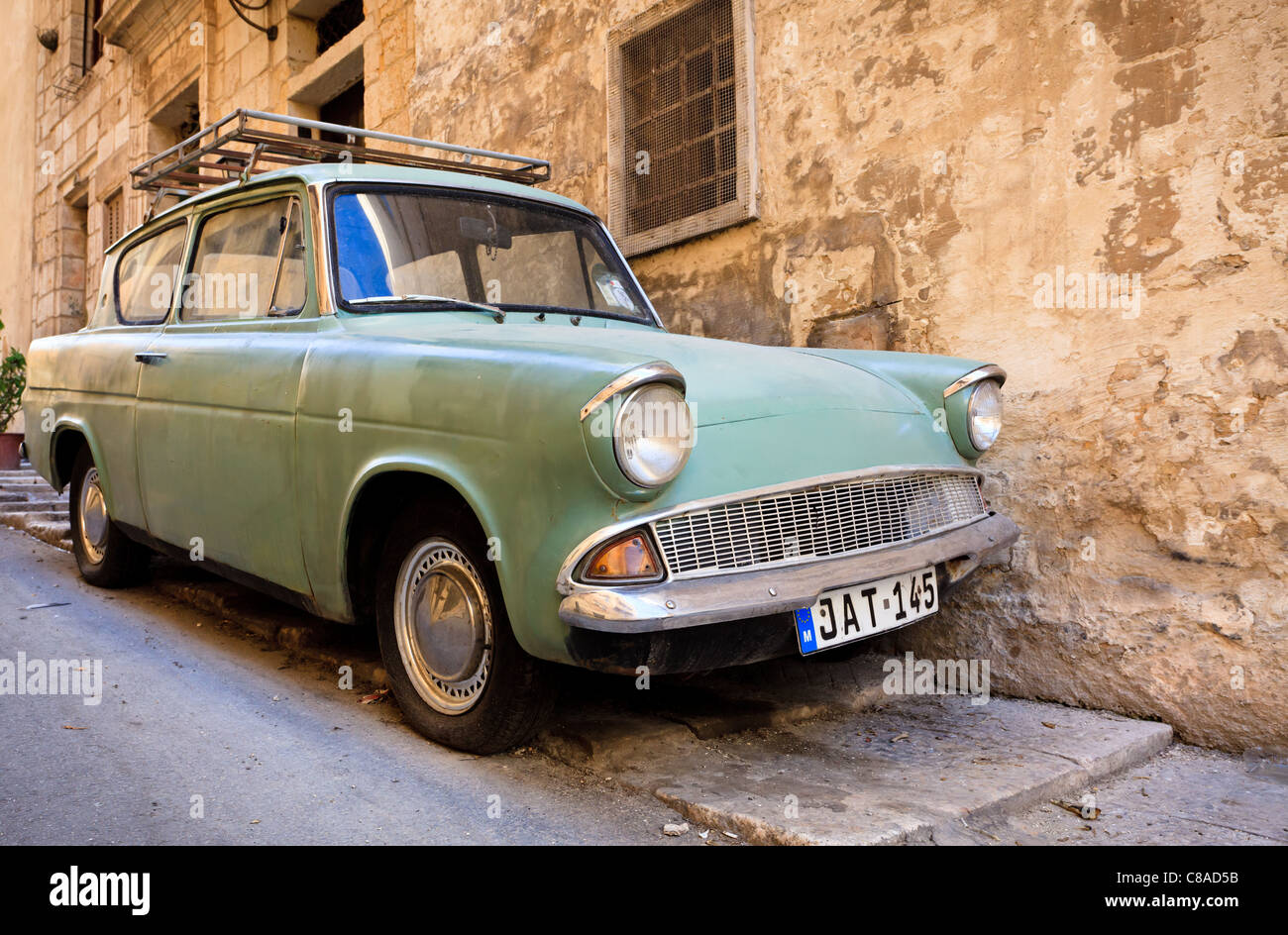 Classic Ford Anglia parked in a narrow street in Valletta, Malta - Stock Image