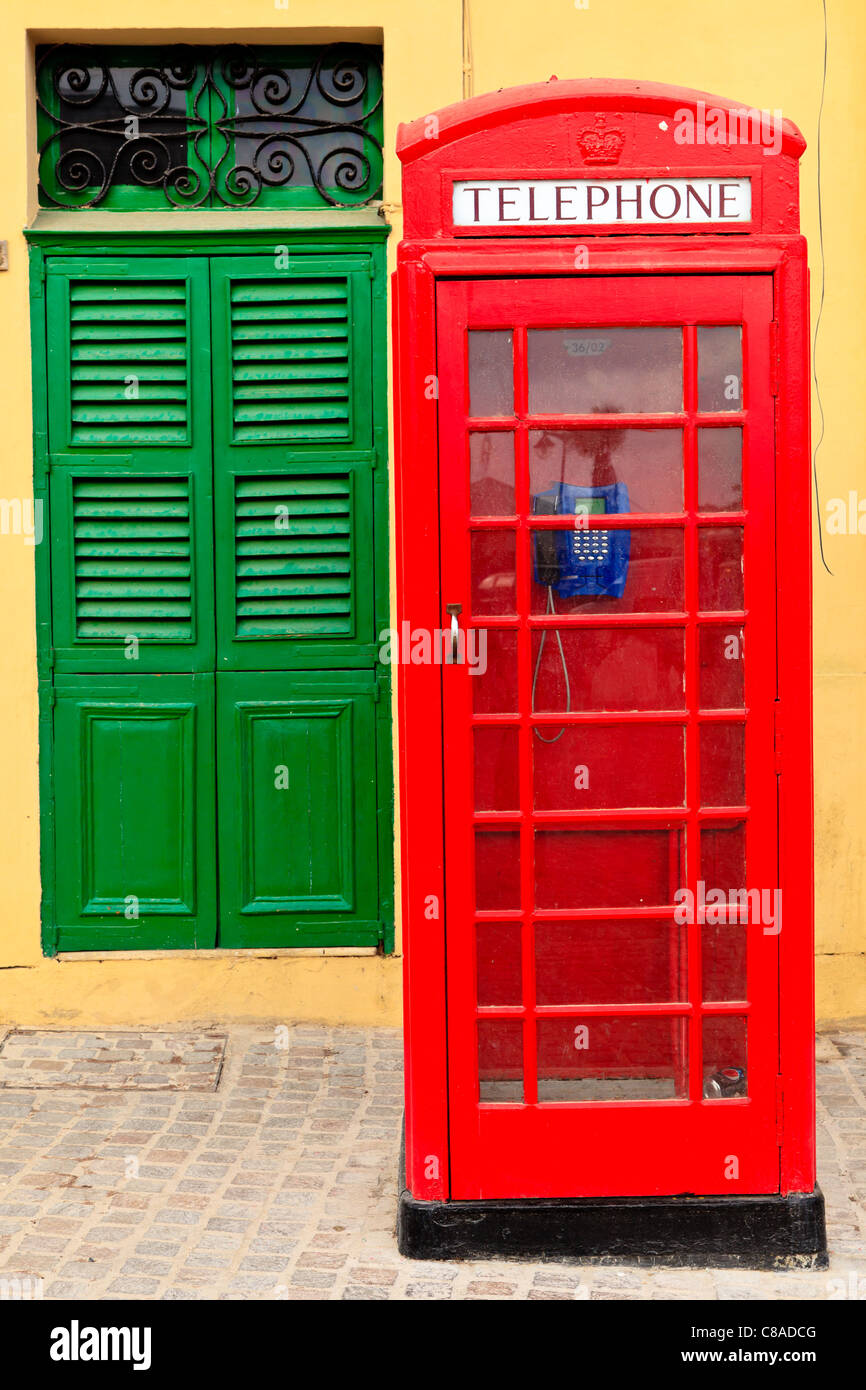 A traditional red English phone in front of yellow wall and a green door, Malta Stock Photo