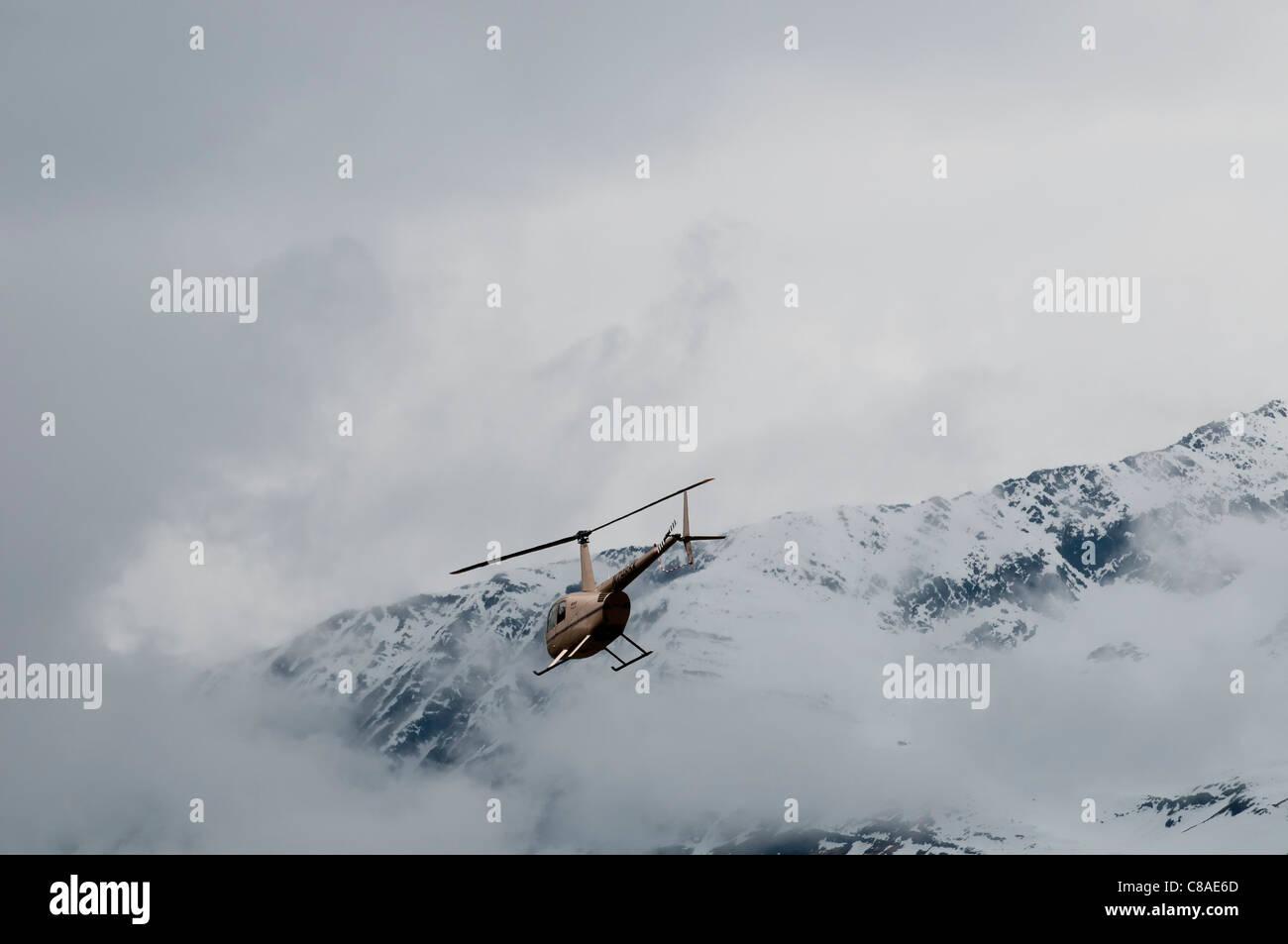 Robinson R44 Raven II helicopter in flight, Valdez Fly-in and Air Show, Valdez, Alaska. - Stock Image