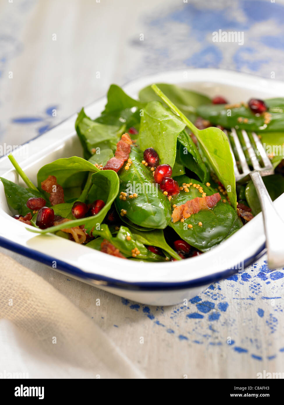 Raw spinach,bacon and pomegrante seed salad - Stock Image