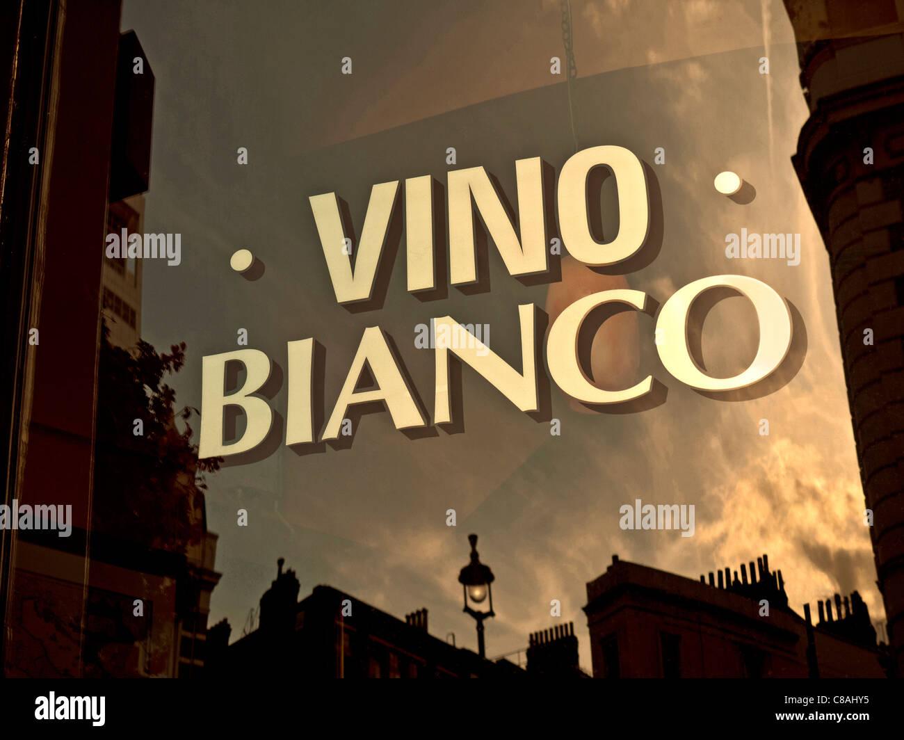 Sign on window of Italian wine bar reflecting sunset promoting Vino Bianco - Stock Image