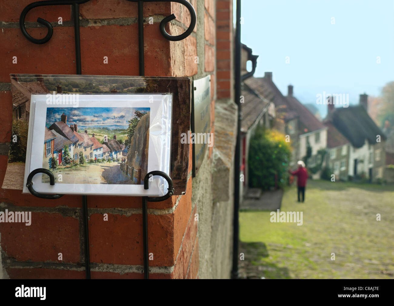 Gold Hill Shaftesbury with local shop tourist postcards in foreground and same view behind Dorset UK - Stock Image
