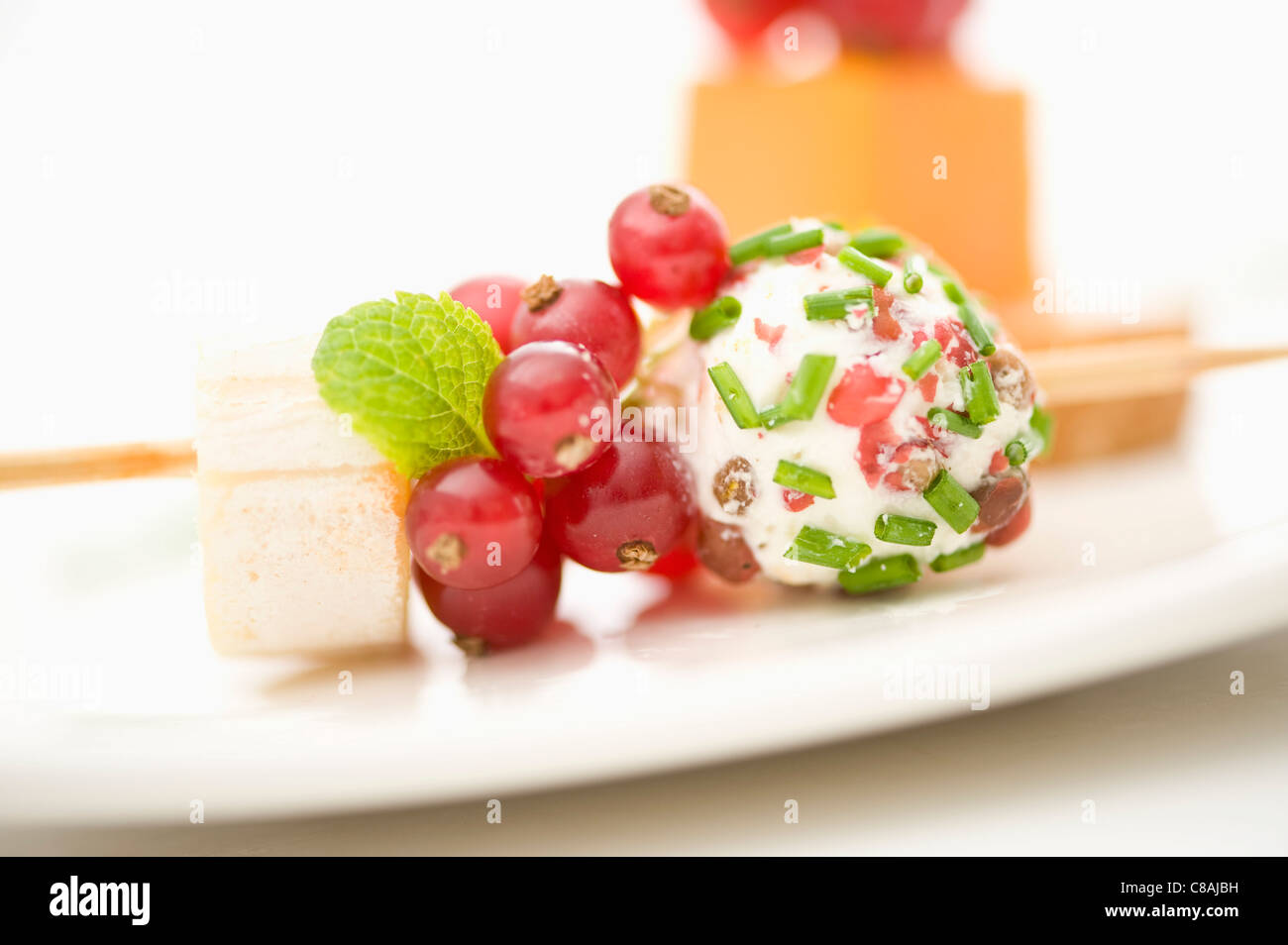 Cheese and red fruit brochette - Stock Image