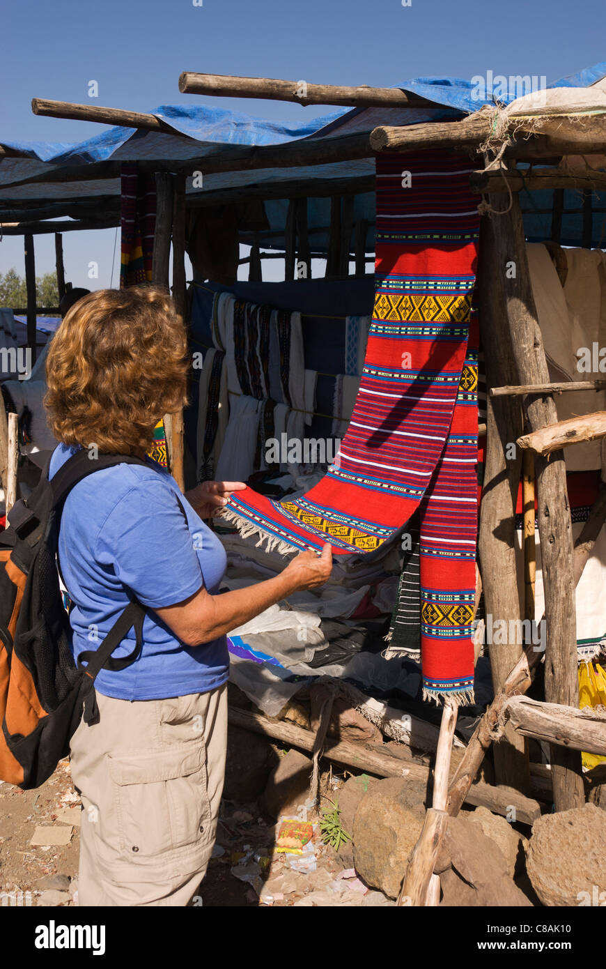 Elk200-3065v Ethiopia, Lalibela, model released Western woman looking at textiles - Stock Image