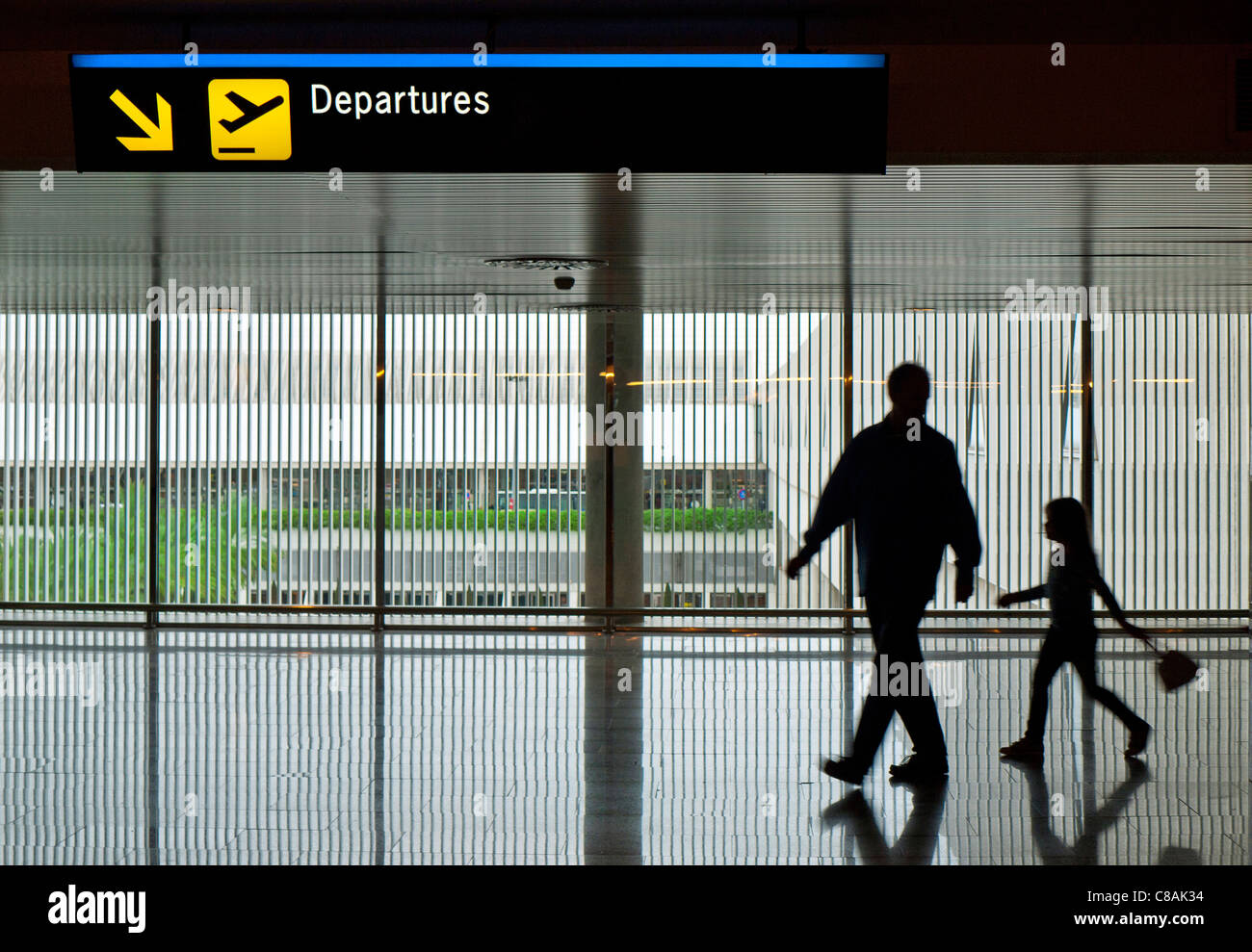 Father and young daughter in silhouette on contemporary concourse walk to airport terminal departures gate - Stock Image