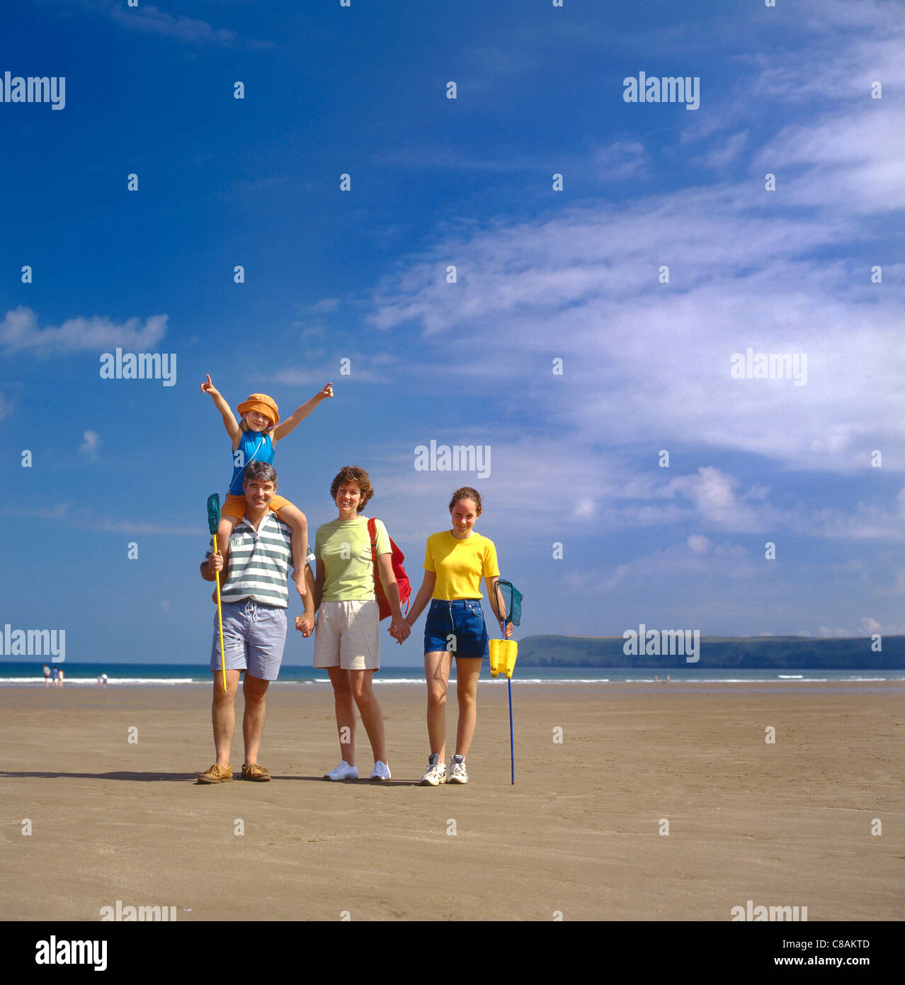Happy young family of four pose together on Woolacombe Beach during their summer vacation in Devon UK - Stock Image