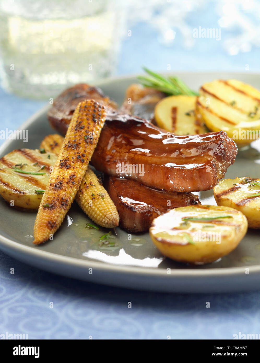 Glazed spare ribs with grilled mini sweet corn on the cobs and potatoes - Stock Image