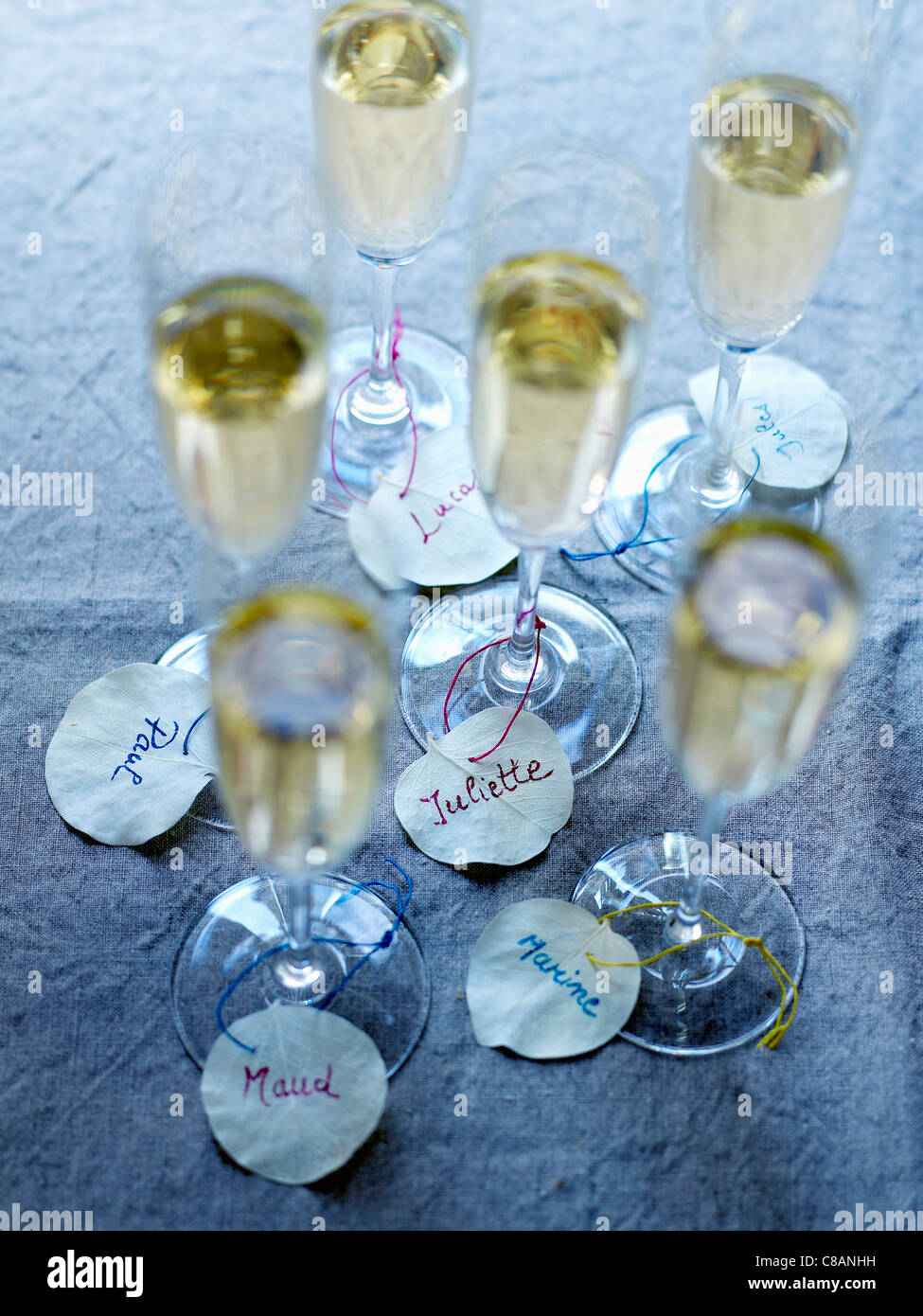 Glasses of Champagne with white leaf name-tags - Stock Image