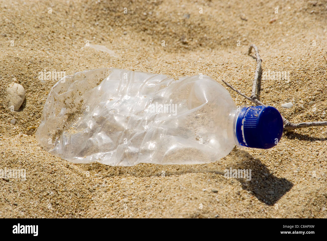 Empty plastic bottle in the sand - Stock Image