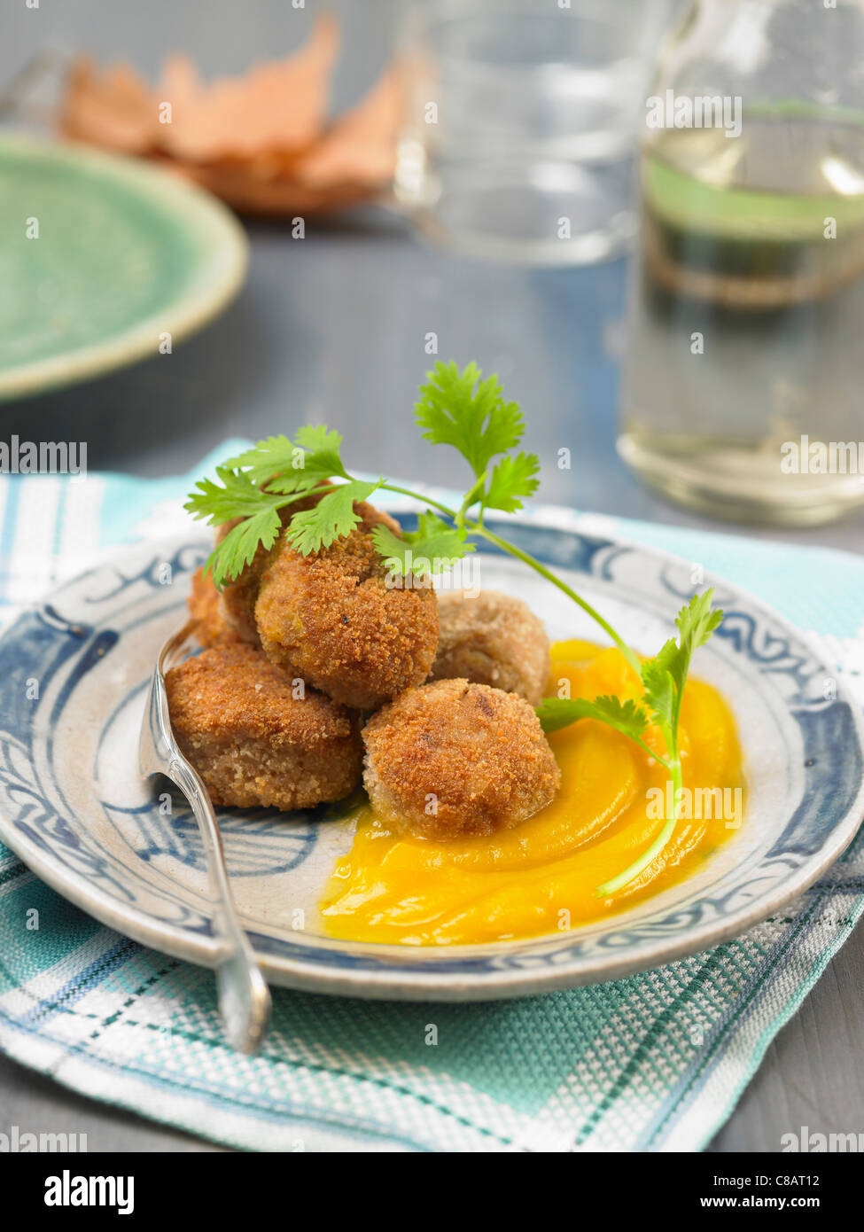 Seitan and smoked tofu balls with pureed pumpkin - Stock Image