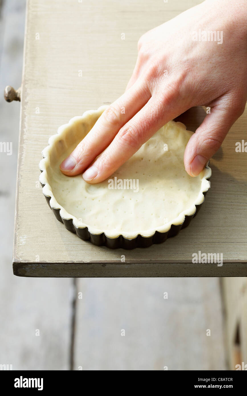 Applying the pastry in the mould - Stock Image