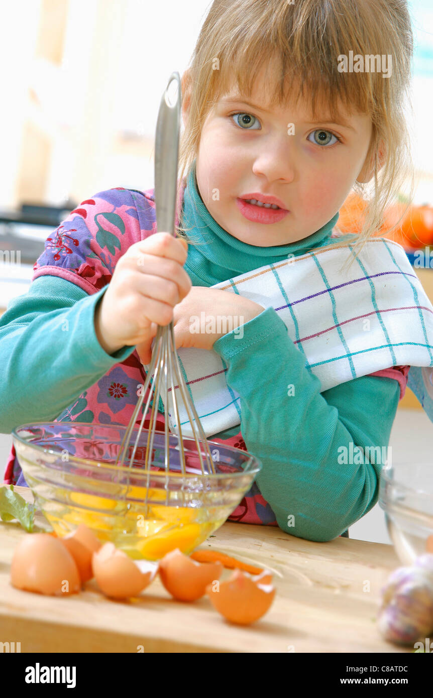Young girl beating eggs - Stock Image