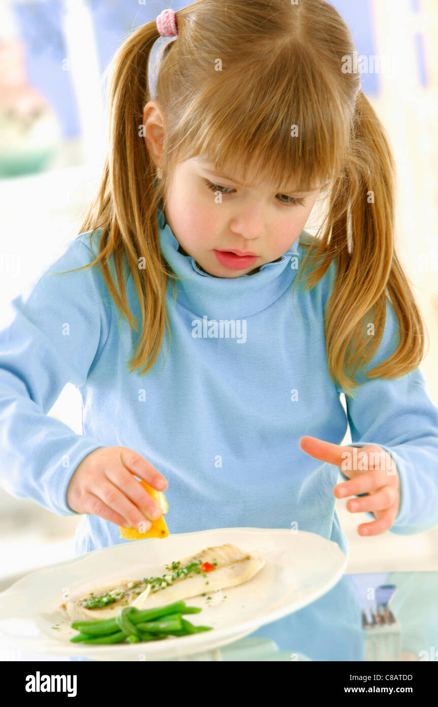 Young girl sprinkling lemon juice onto a plate of fish - Stock Image