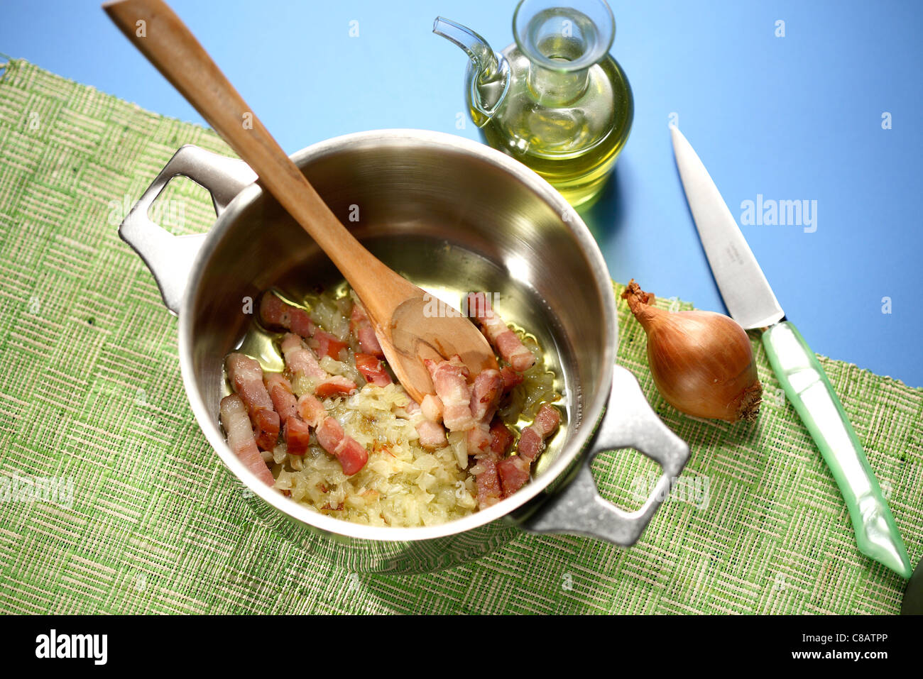 Cooking the diced bacon and onions in a casserole dish - Stock Image