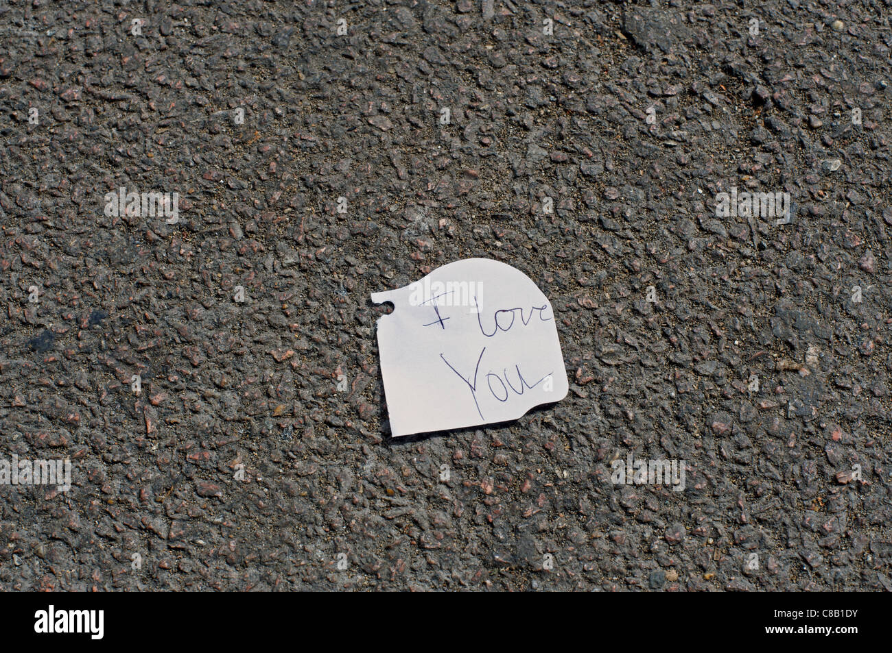 A small piece of paper with the words 'I love you' left on a railway
