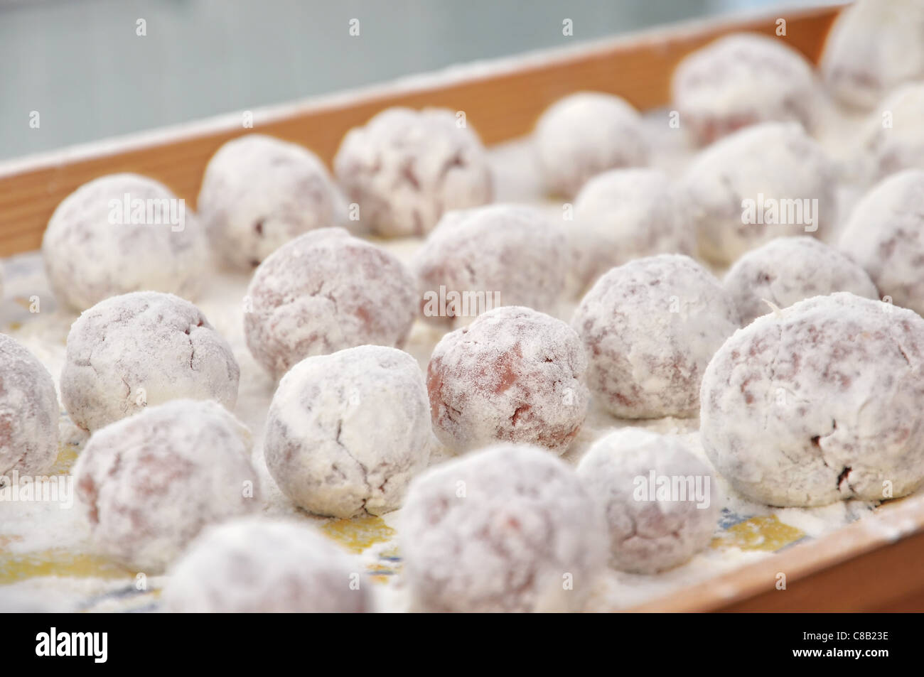 Meat balls in the flour on a tray ready to be cooked - Stock Image