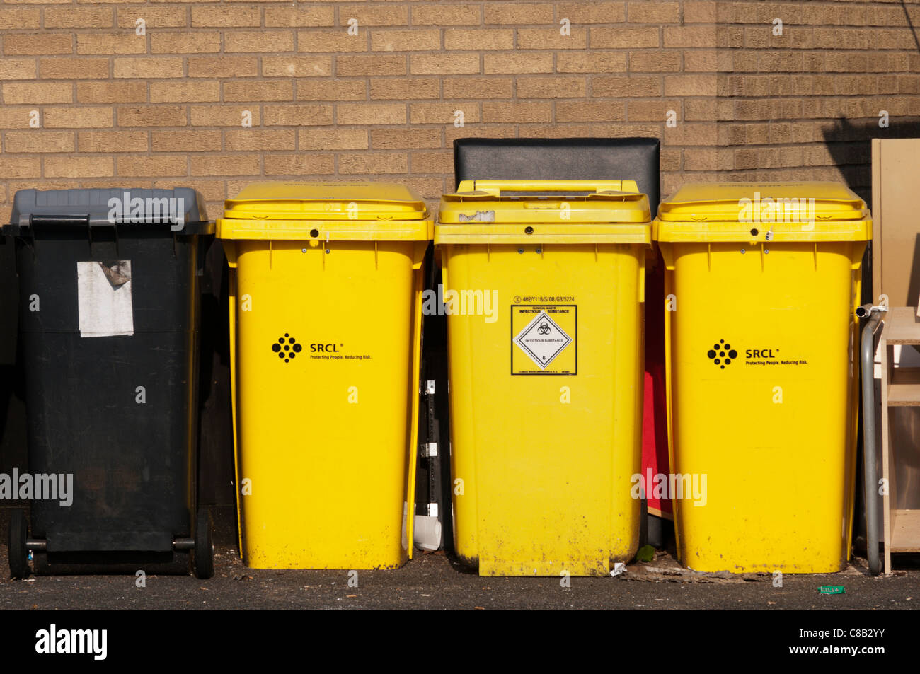 Yellow wheelie bins for clinical waste or infectious substances. - Stock Image