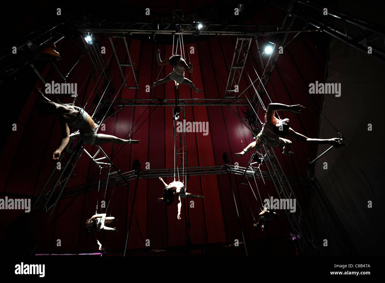 Suspended high wire artists practising with the Nofitstate Circus on tour in South Wales UK - Stock Image