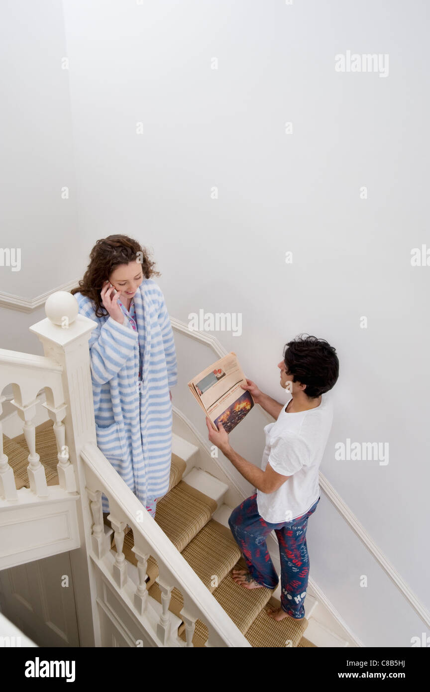 Man and woman busy in their daily routine - Stock Image