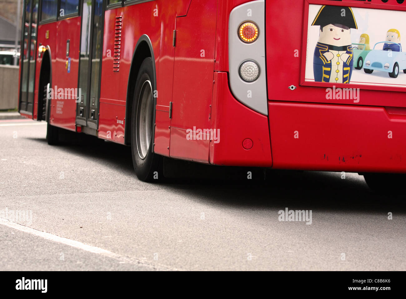 part of a double decker red London bus as it travels along a road - Stock Image