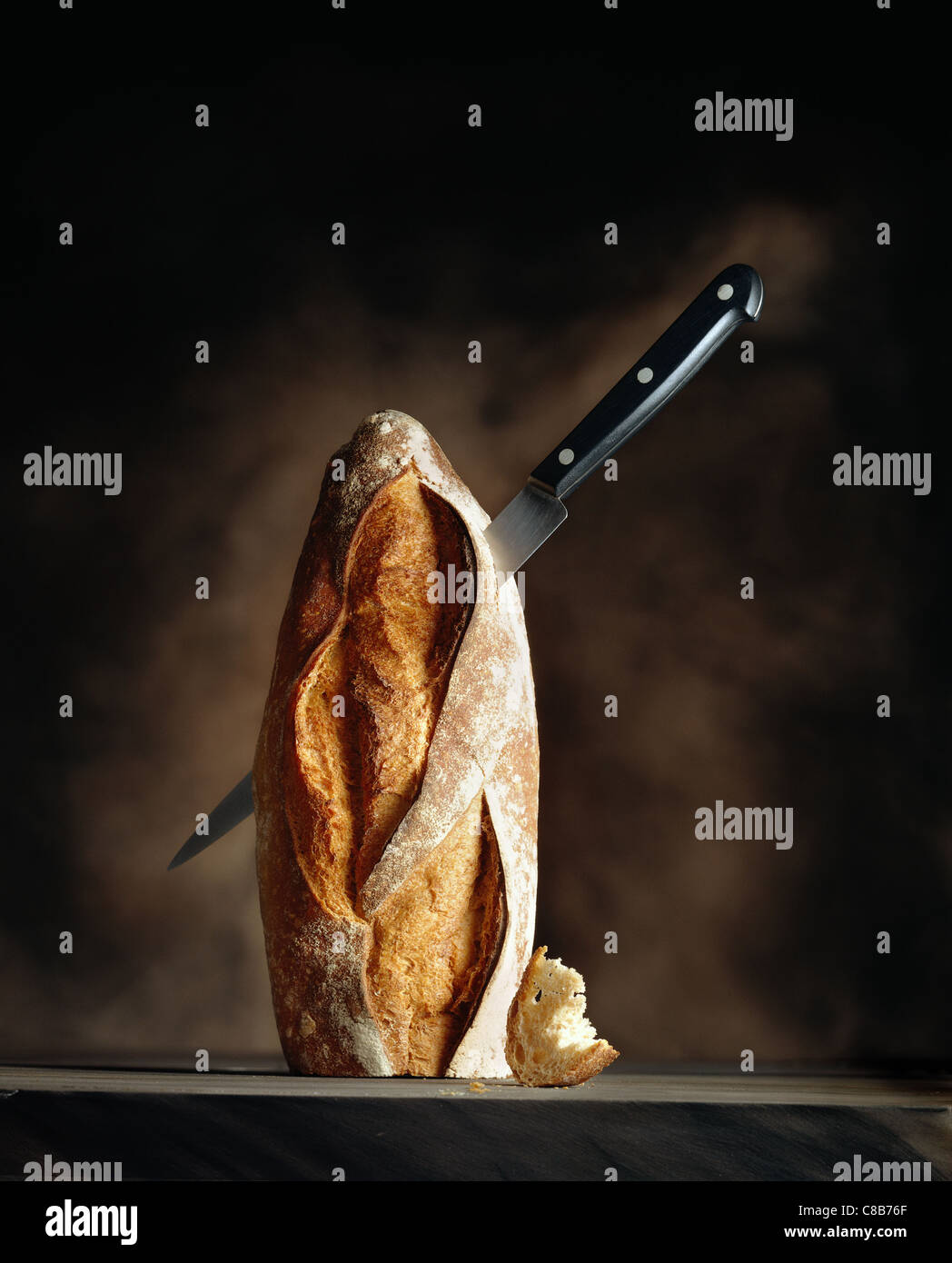 upright loaf of bread with knife - Stock Image