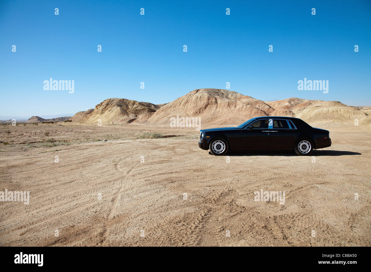 Luxury car parked on unpaved road near mountains - Stock Image