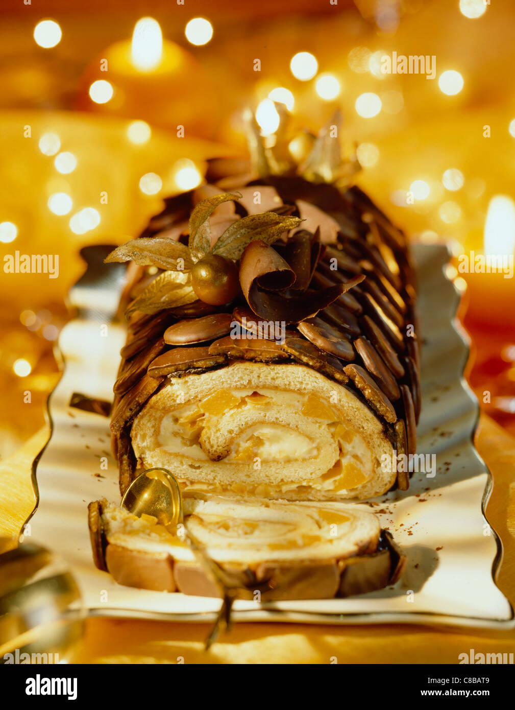 Crunchy chocolate-coated, orange and peach Yule log - Stock Image
