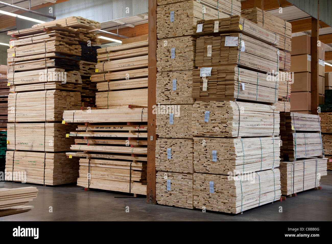 Stacks of plywood piled up in warehouse - Stock Image