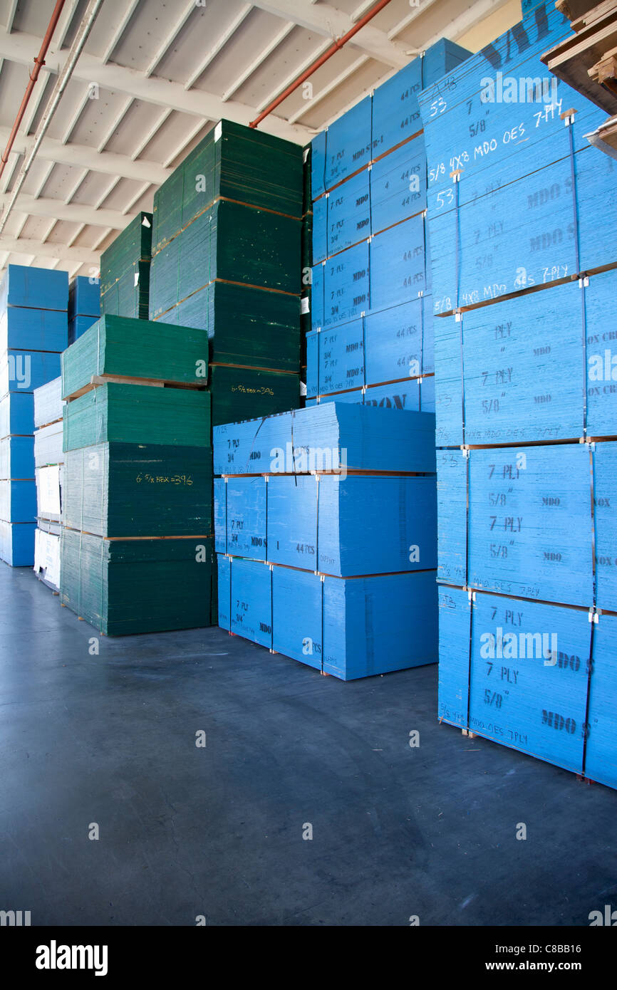 Blue boxes piled up of in warehouse - Stock Image