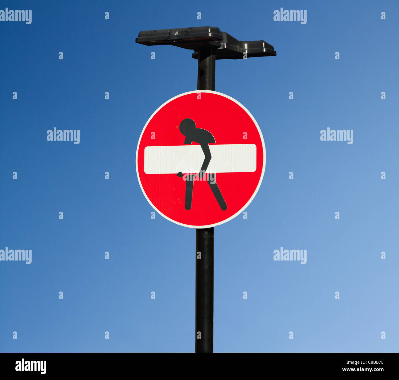 A no entry road sign which has been artistically modified with a person trying to lift the white bar. Shoreditch, - Stock Image