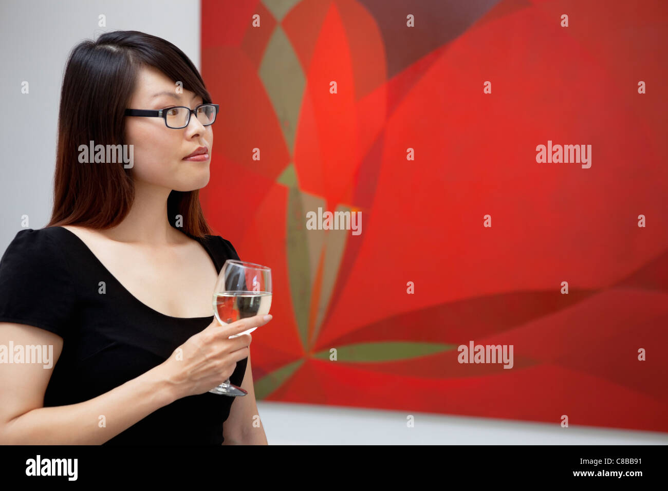 Young woman looking at wall paintings in art gallery - Stock Image