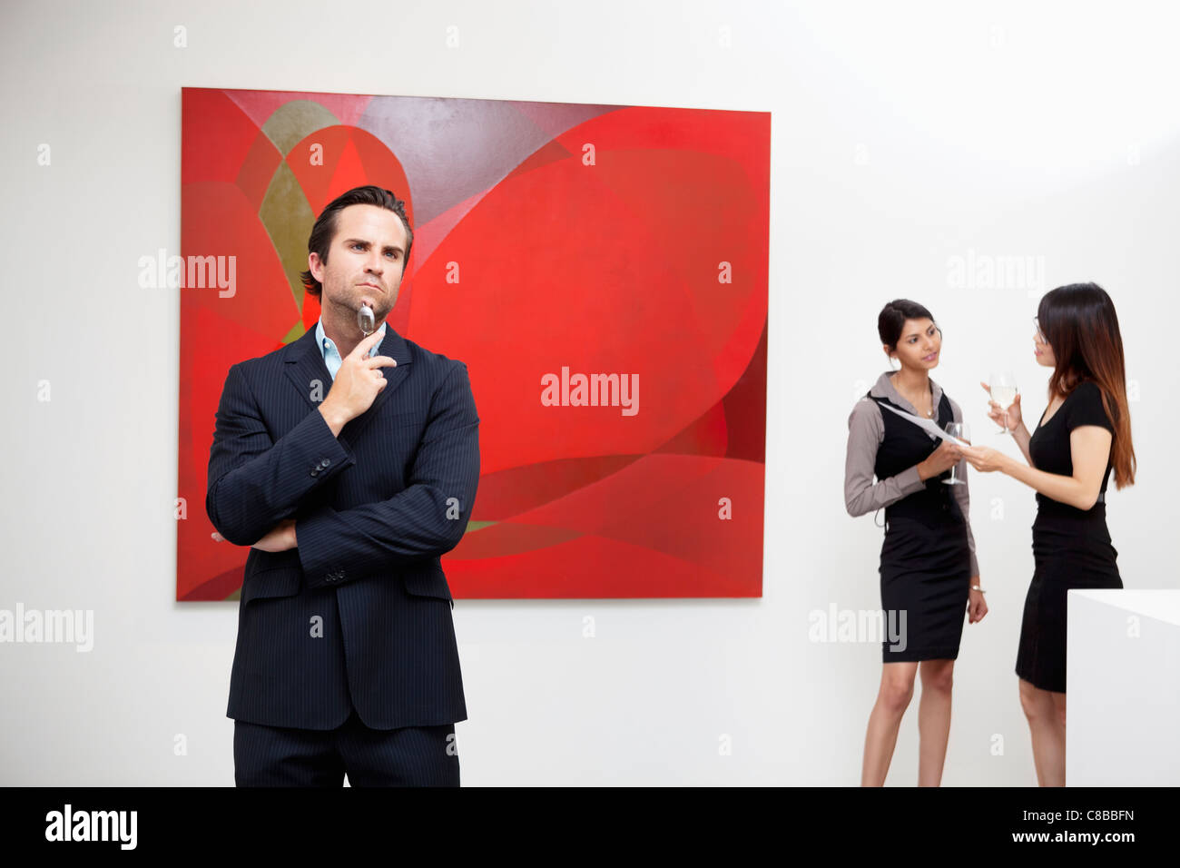 Young man thinking with two women talking in background in art gallery - Stock Image