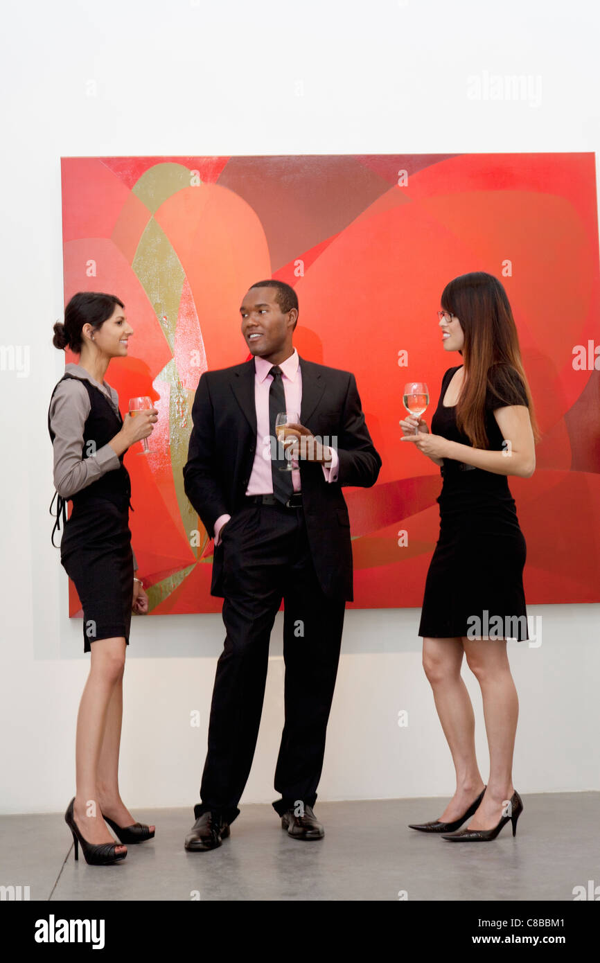 Young executives having a conversation in front of painting in art gallery - Stock Image