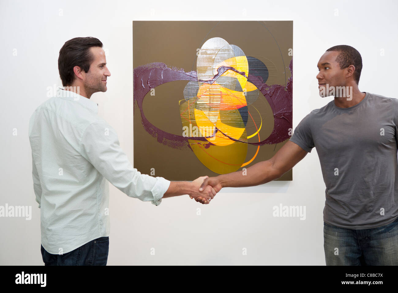 Two man in casuals shaking hands in front of wall painting - Stock Image