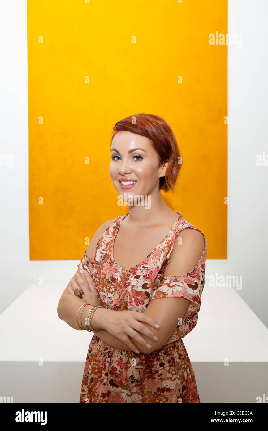 Half-length portrait of young woman in front of yellow painting - Stock Image