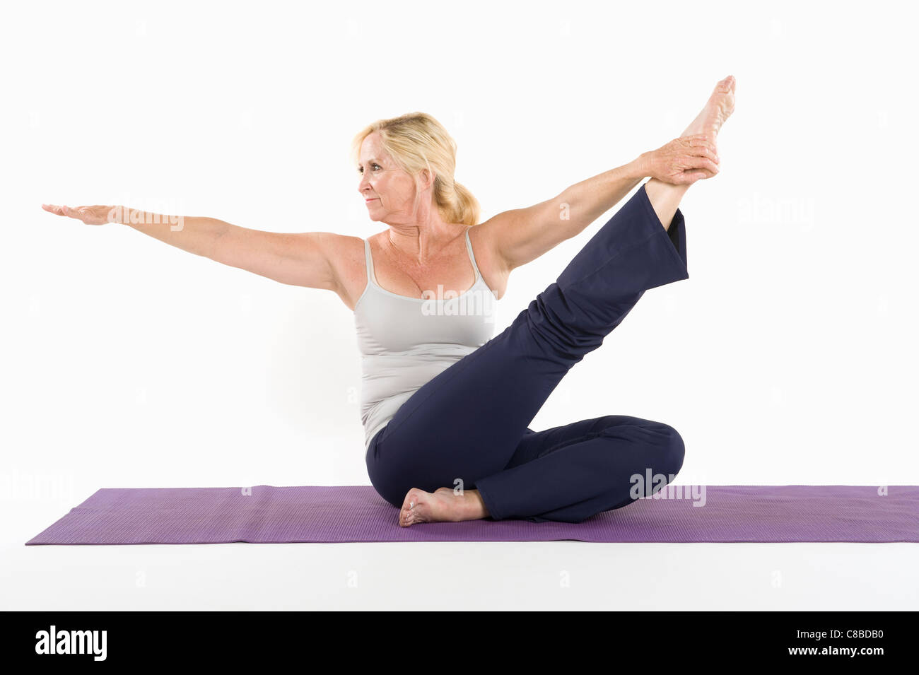 Middle aged woman doing yoga over white background - Stock Image