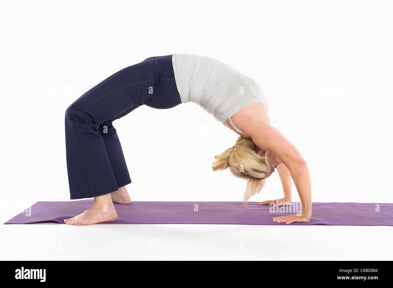 Woman in backbend yoga pose - Stock Image