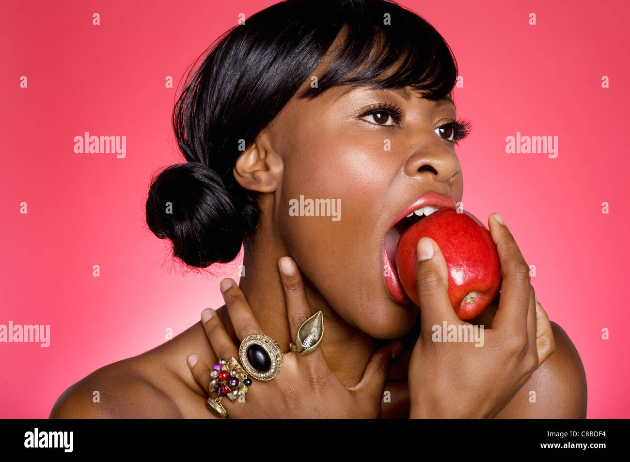 Close up of woman biting an apple over colored background - Stock Image