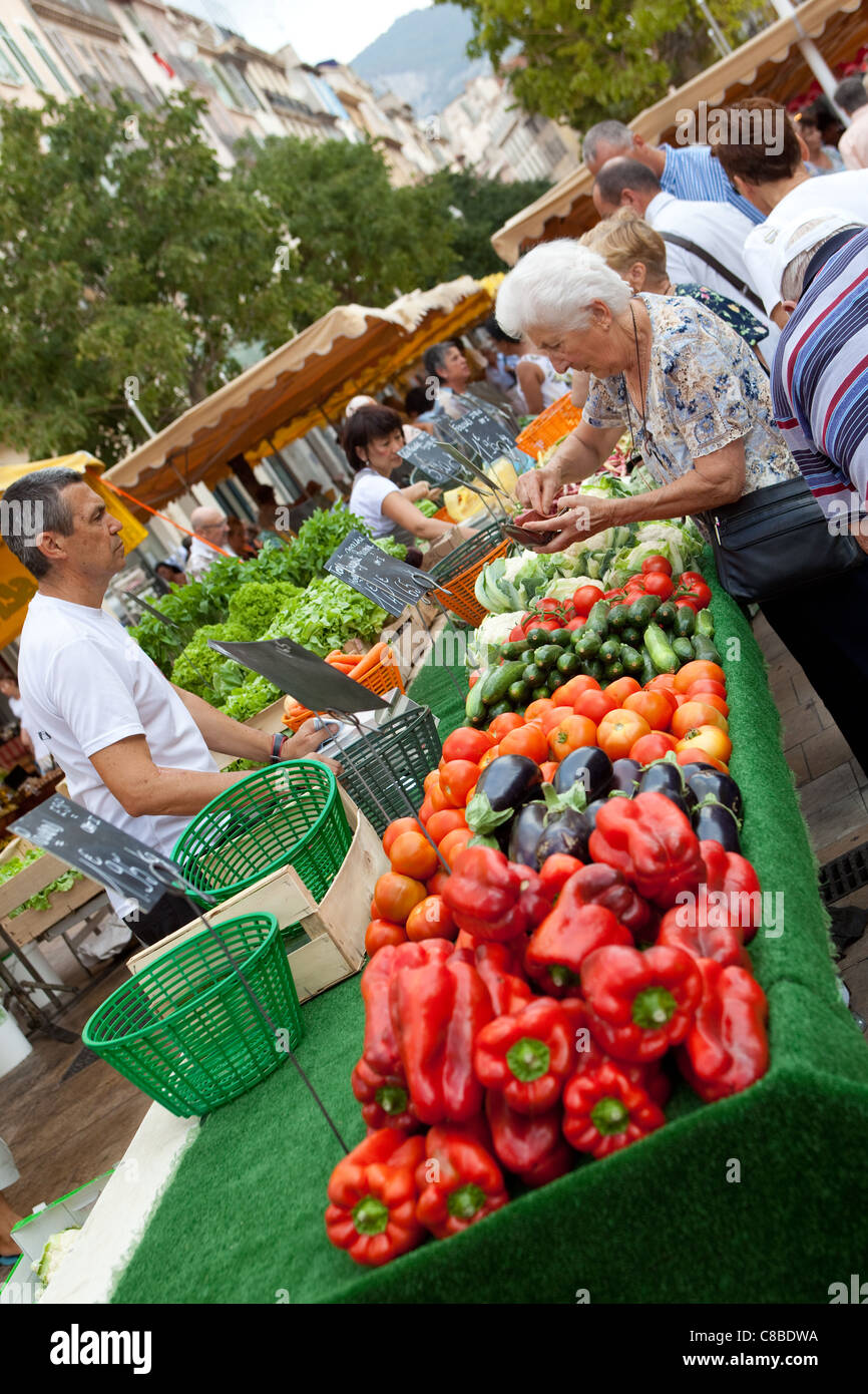 Senior citizen, shopping for value, buying vegetables and money exchanging hands,  at the market place Toulon France - Stock Image
