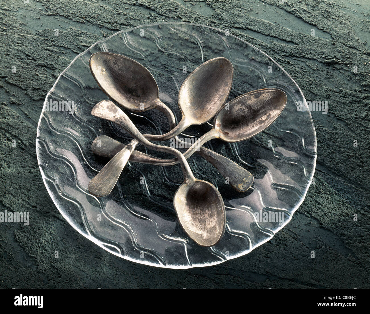Bent spoons on plate - Stock Image