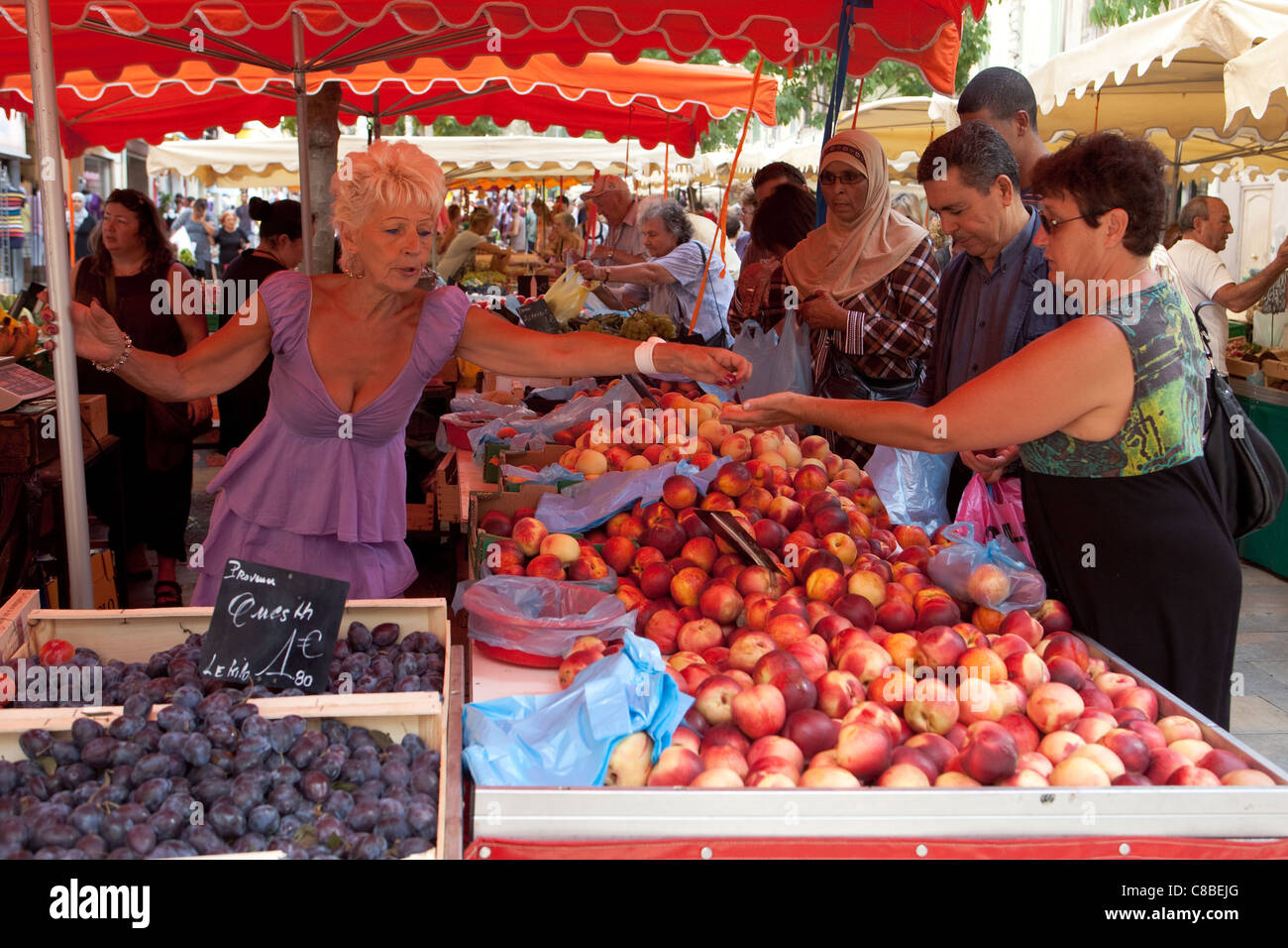 customer buying fruit and money exchanging hands at the market place Toulon France - Stock Image